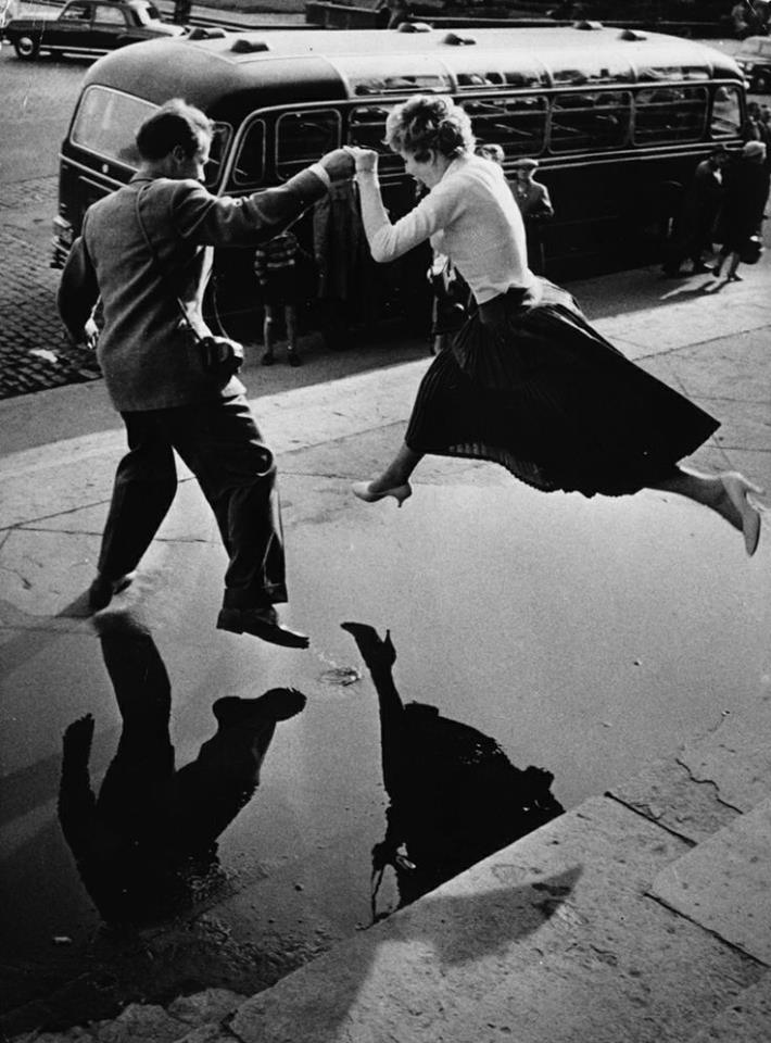 A man gives a woman a helping hand as she takes a flying leap over a large puddle on the pavement.